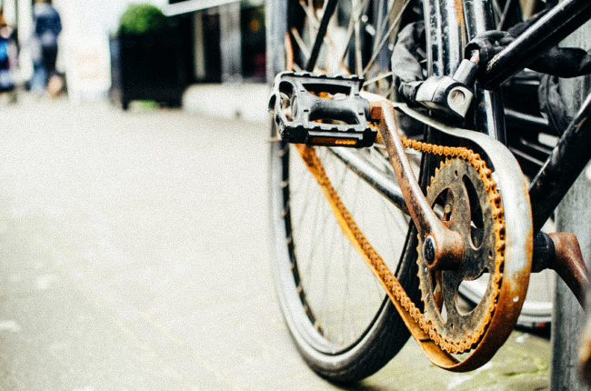 Rusted bike chain that needs maintenance in order to work further. Concept of wrong expectations - work without maintenance and investment in development.